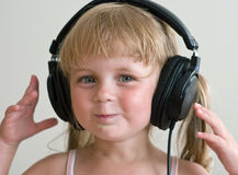 Kid with headphones. Cute girl listening music at headphones Royalty Free Stock Images