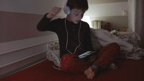 Kid with headphones dancing while looking at the tablet stock footage
