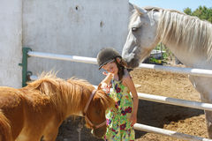 Kid in helmet stroking pony Royalty Free Stock Photos