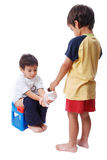 Kid is helping another one on toilet. Cute kid is sitting on toilet and taking toilet paper Stock Photography