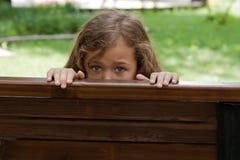 Kid Hiding Behind A BenchIn. stock photo