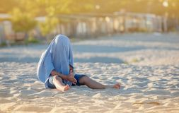 Hiding Kid. A kid hiding in his father`s t-shirt on a sandy beach Royalty Free Stock Image