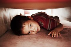 Kid hiding under bed. Playful little boy hiding under bed Royalty Free Stock Photos