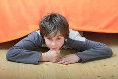 Kid hiding under bed. Kid - smiling boy hiding under orange cover of bed while lying on wooden floor Royalty Free Stock Photo