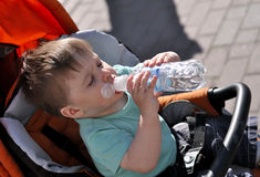 Kid himself drinks water from a bottle in a stoller. Kid himself drinks water from a bottle in stoller Royalty Free Stock Photography
