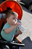 Kid himself drinks water from a bottle in a stoller. Kid himself drinks water from a bottle in stoller Royalty Free Stock Photos