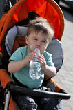 Kid himself drinks water from a bottle in a stoller. Kid himself drinks water from a bottle in stoller Royalty Free Stock Images