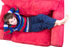 Kid in his Comfort Zone. Young boy in his comfort zone, laying down on the red couch comfortably bare foot royalty free stock photo