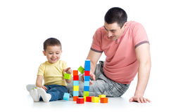 Kid and his dad play with building blocks Stock Photo