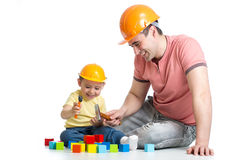 Kid and his dad play with building blocks. Kid and his dad playing with building blocks Royalty Free Stock Images