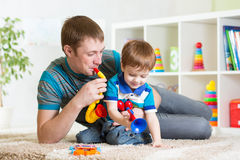 Kid and his dad play musical toys. At home stock photography