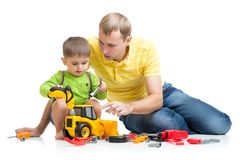 Kid and his dad repair toy tractor Stock Photo