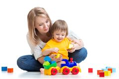 Kid with his mom play building blocks toys. Happy family - toddler boy and mother play building blocks Royalty Free Stock Photography