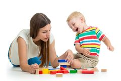 Kid and his mom play toys together. Isolated on white Royalty Free Stock Image