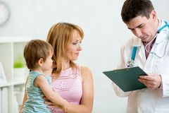 Kid and his mother consulting with the doctor in Stock Images