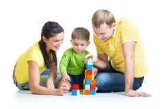 Kid with his parents play building blocks Stock Images