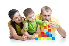 Kid with his parents play building blocks Stock Image