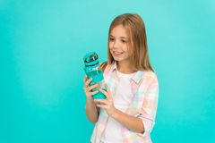 Kid hold bottle blue background. Child girl long hair has water bottle. Water balance concept. Healthy and hydrated. Pediatric disorders of water balance. Girl stock image