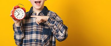 Kid holding alarm clock and pointing on it, isolated on yellow. Morning time. Copy space. Time concept. Nearly 7 hour in morning. stock photography