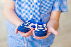 Kid holding baby shoes Stock Photo