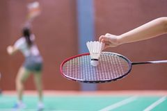 Kid holding badminton racket and shuttlecock in badminton court.  royalty free stock image