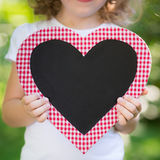 Kid holding blackboard. In heart shape outdoors. Spring holiday concept stock images