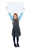 Kid holding blank billboard above her head Stock Photography