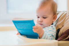 Kid holding a blue book in the hands Royalty Free Stock Image