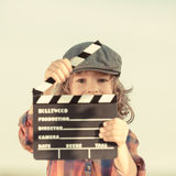 Kid holding clapper board in hands. Cinema concept. Retro style stock images