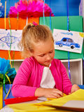 Kid holding colored paper on table in kindergarten . Portrait of school child girl make of colored paper on table in primary school Royalty Free Stock Image
