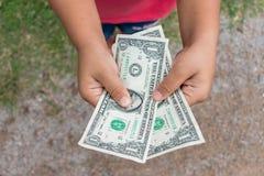 Kid holding dollars money. Asian kid holding dollars money Royalty Free Stock Images