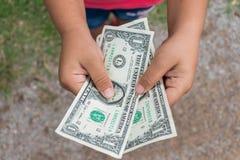 Kid holding dollars money. Asian kid holding dollars money Stock Photos