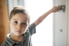 Kid holding the door at home smiling. A Kid holding the door at home smiling stock photos