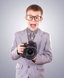 Kid holding a dslr camera on a blue background Stock Image