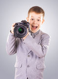 Kid holding a dslr camera on a blue background Royalty Free Stock Photo