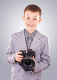 Kid holding a dslr camera on a blue background Royalty Free Stock Photos
