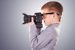 Kid holding a dslr camera on a blue background Stock Photo