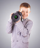 Kid holding a dslr camera on a blue background Royalty Free Stock Image