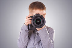 Kid holding a dslr camera on a blue background Royalty Free Stock Photography