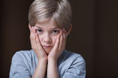 Kid holding face between hands Stock Images