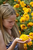 Kid holding flower. A white caucasian girl child sitting amongst yellow flowers Royalty Free Stock Photography