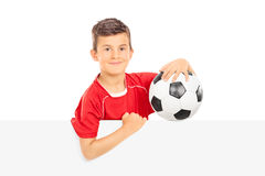 Kid holding a football behind a blank panel Royalty Free Stock Photography