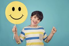 A kid holding a happy emoticon face. A kid holding a yellow circle with smile face emoticon stock photos