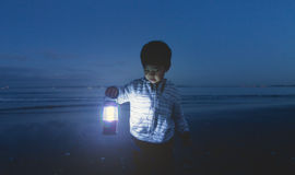 Kid Holding Lamp. Royalty Free Stock Photos