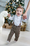 The kid is holding mom`s hands near Christmas tree. Little boy with huge brown eyes,blond short hair,wearing light brown trousers with suspenders and white Royalty Free Stock Photography