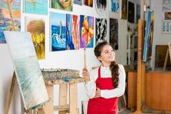 Kid holding painting brush and looking away in workshop of. Art school stock photo