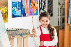 Kid holding painting brush and looking at camera in workshop of. Art school royalty free stock photo