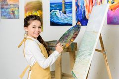 Kid holding palette and looking at camera in workshop of. Art school royalty free stock photography
