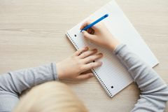 Kid holding pen and writing. stock photography