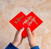 Kid holding red pockets shaped like a heart stock photos